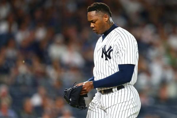 Aroldis Chapman walks to the dugout after being pulled in the 10 inning in the Yankees' 3-2 loss Sunday. (MIKE STOBE/GETTY IMAGES)